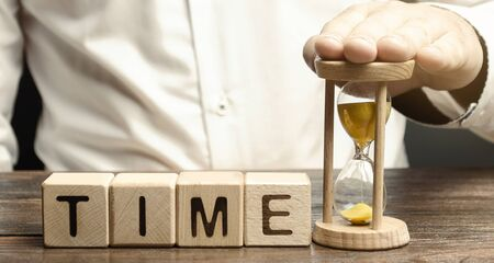 A man puts hourglass near wooden blocks with the word Time. Concept of time management and proper distribution. Planning business and work. Business youth. Analysis of working time. Deficit