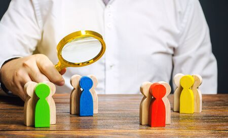 Groups of multicolored wooden people and businessman. The concept of market segmentation. Target audience, customer care. Market group of buyers. Customer relationship management. Selective focus Banque d'images