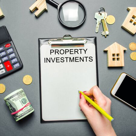 Table with wooden houses, calculator, coins, magnifying glass with the word Property investments. Attracting investment in your home. Repair planning. Improving the quality of life. Financial concept