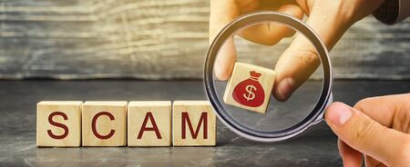 Businessman puts wooden blocks with the word Scam. Fraudulent investment project. Illegal plan to get money. Cheating people. Raw deal. Financial Pyramide. Hacker attack