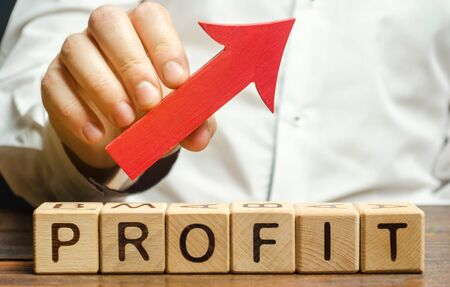 Holzklötze mit dem Wort Profit und einem Pfeil nach oben. Konzept des Geschäftserfolgs, des finanziellen Wachstums und des Reichtums. Erhöhen Sie die Gewinne und den Investmentfonds. Leistung. Profitables Geschäft. ROR, ROI