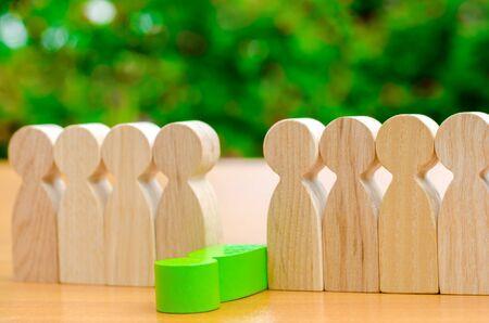 La figura verde de un hombre se sale de la fila de personas. Concepto de despido de empleados y gestión de equipos en una empresa comercial. Unión debil. Toxicidad del personal. Mal trabajador. Degradar. Enfoque selectivo disparado