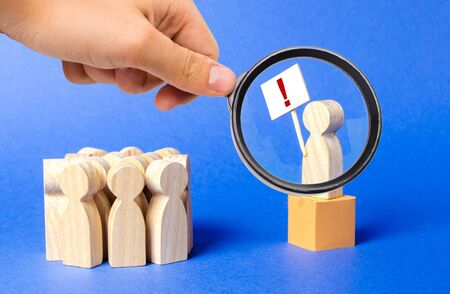 A magnifying glass looks at a person with a poster exclamation mark is on the box and draws the publics attention to the problem. Social tension, strike. Raising the question of the correctness
