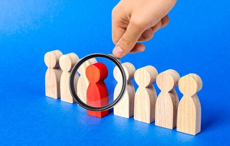 A magnifying glass looks at a red figure person comes out of people line. Leadership qualities, talented employee. HR is looking for new employees, choice among candidates. A suitable candidate Stok Fotoğraf