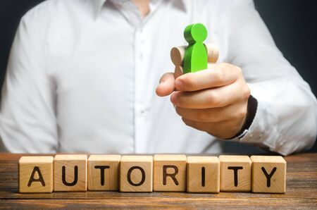 A man holds figures of people in a fist and the word Authority. High status and respect, reputation and importance. Business leader or crime boss. Submission and management control employees