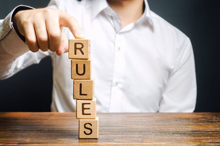 A man holds a tower of blocks with the word Rules from falling. Setting clear rule and restrictions. Leadership and discipline. Authoritarianism, tight control framework. Norms and laws in society
