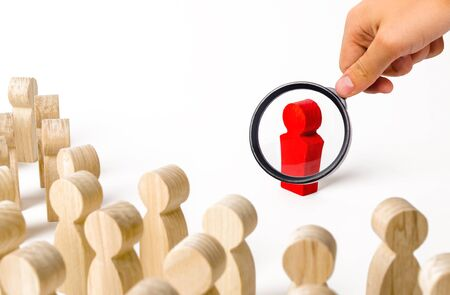 A magnifying glass looks at a red figurine of a man near a crowd. Leader, leadership and initiator of action. work or business organization. team building. Idol and example to follow. Distrust Stok Fotoğraf