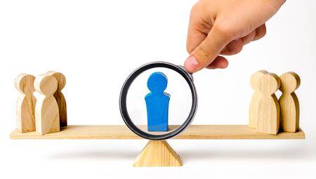Una lente d'ingrandimento guarda un leader in piedi sulla bilancia tra due gruppi di persone. Risolvere situazioni di conflitto. L'unione di due schieramenti opposti. Servizi di arbitro e mediatore.