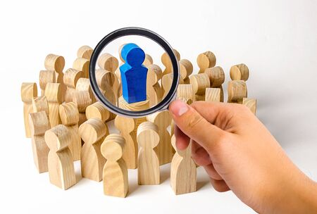 A magnifying glass looks at the blue figure of a man in the center of a crowd of people. Leadership and team management, an example for imitation. Loyalty and trust. Idol followers Banque d'images