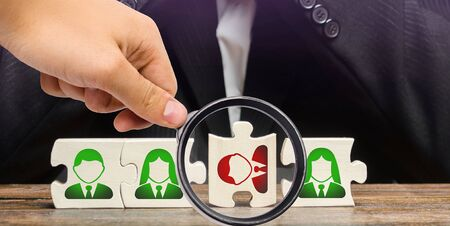 A magnifying glass looks at a businessman sitting in despair over the not assembled puzzles symbolizing a team of employees. Toxic or incompetent worker who fails to comply tasks and disrupts
