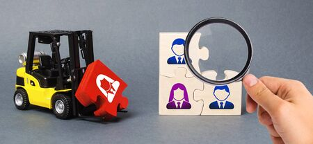 A magnifying glass looks at a red puzzle to the unfinished assembly of business team. Search, recruitment staff, hiring leader. Creating an efficient and productive business unit. Leadership 스톡 콘텐츠