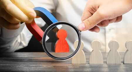 A magnifying glass looks at a businessmans hand draws a red figure from the team with a magnet. The concept of toxic and non-competent worker. Increase team efficiency. leader forms a team.