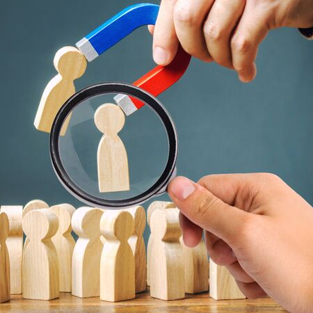 A magnifying glass looks at a magnet pulling wooden figures of people from the crowd. Recruiting new workers, headhunters. Formation of a new business team of applicants. Personnel Management.