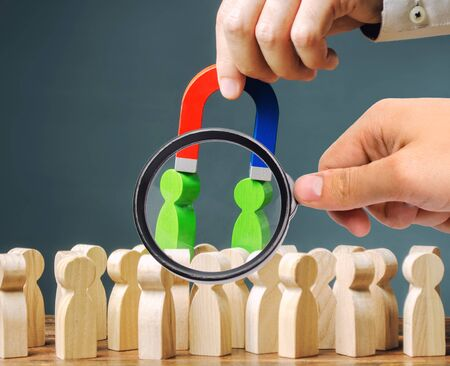 A magnifying glass looks at a magnet pulls green figures of people out of the crowd. Recruiting new workers. Formation of a new business team. Search talented workers with great career potential