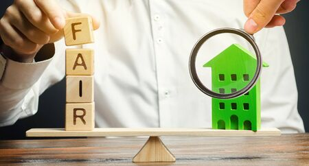 Wooden blocks with the word Fair and a wooden house. Fair value of real estate and housing. Property valuation. Home appraisal. Housing evaluator. Legal transparent deal. Apartment purchase  sale.