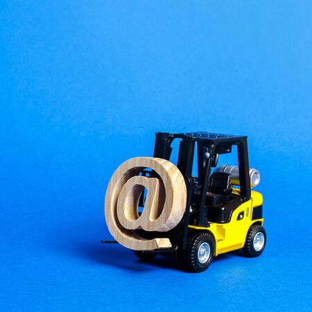 Yellow Forklift truck carry email symbol commercial AT. Integration of the industry into network technologies and Internet. E-commerce. sales of goods through online trading platforms. shopping online