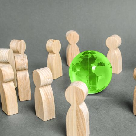 People surrounded a green Globe world planet earth. Cooperation and collaboration of people around the world. Outsourcing and joint work on projects. Diplomacy. crowdfunding. Preserving environment
