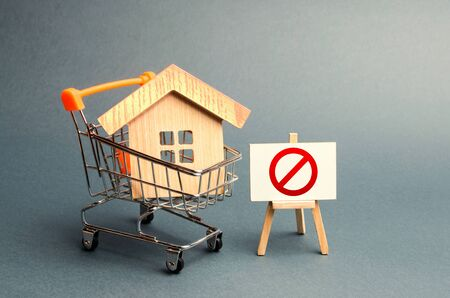 House in the shopping cart and the sign of the ban NO. Inaccessible and expensive housing. Seizure and freezing of assets by a bank, court. Unavailability of housing, busy or low supply