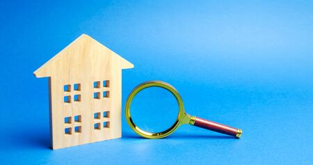 Magnifying glass and wooden house. House searching concept. Home appraisal. Property valuation. Choice of location for the construction. Search for housing, apartments. Real estate appraiser services Banco de Imagens