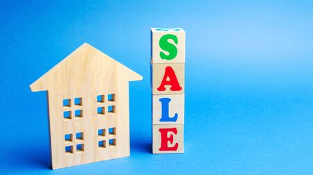 Wooden blocks with the word Sale and wooden miniature house. The concept of the sell of real estate, apartments and residential premises. Rent and mortgage. Market analysis
