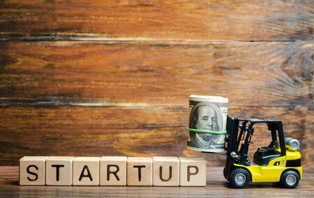 Forklift truck carries a bundle of dollars to inscription Startup. The concept of raising funds for a startup. Crowdfunding. Raising funds and resources to complete a commercial or intangible project.