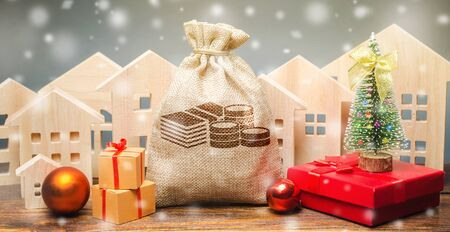 Money bag, wooden houses, Christmas tree and gifts. Christmas Sale of Real Estate. New Year discounts for buying housing. Purchase apartments at a low price. Holiday discounts. Favorable prices Stock Photo