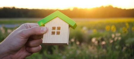 Casa in legno nelle mani sullo sfondo del tramonto. Concetto di bene immobile. Casa ecologica. Simbolo di vita familiare felice. Compra un alloggio fuori città. Cerca hotel in vacanza. Messa a fuoco selettiva