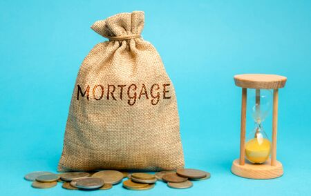 Money bag with the word Mortgage and hourglass. Mortgage rates concept. Loan and credit. Interest payment. Business and finance. Real estate, housing Stok Fotoğraf
