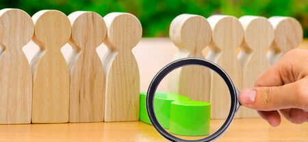 The green figure of a man falls out of the line of people. Concept of employee dismissal and team management in a business company. Weak link. Staff toxicity. Bad worker. Demote. Fired Selective focus