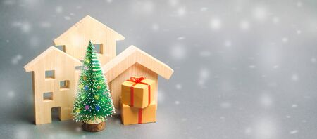 Wooden houses, Christmas tree and gifts. Holiday. Winter vacation. Christmas Sale of Real Estate. New Year discounts for buying housing. Purchase apartments at a low price.