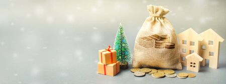 Money bag, wooden houses, Christmas tree and gifts. Christmas Sale of Real Estate. New Year discounts for buying housing. Purchase apartments at a low price. Holiday discounts. Favorable prices Banner