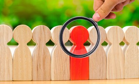 Wooden figures of people. The red man comes out with a team of workers. The concept of choosing a new leader. Choice of person. Hiring and recruiting. Human resource management. Selective focus