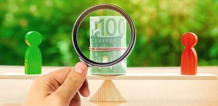 Holzfiguren von Menschen auf Waagen und Euro-Banknoten dazwischen. Das Konzept der Geldtrennung. Eigentumsteilung. Scheidung und Rechtsberatung. Geschäftskonflikt. Finanzielle Auseinandersetzung Standard-Bild