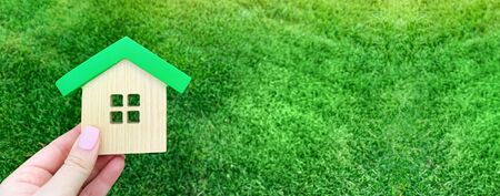 Miniature wooden house on green grass. Real estate concept. Eco-friendly and energy efficient house. Buying a home outside the city. The urban downshift. Nature. Fresh air. Mortgage, loan. Property