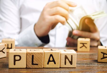 Wooden blocks with the word Plan and money in the hands of a businessman. Strategy planning. Management business concept. Improving the efficiency of the company's sales. Achieving financial target