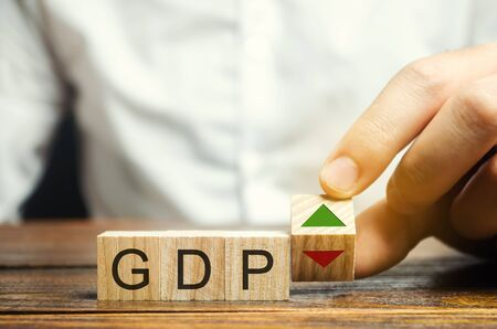 Wooden blocks with the word GDP and up and down arrows. An unstable economy in the country. Financial measure of the market value of all the final goods and services produced in a specific period.