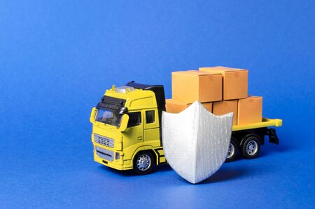Yellow truck with cardboard boxes covered by the shield. Cargo insurance, transportation safety. Guaranteed quality and speed of delivery, security of goods. Transport valuable and dangerous products.