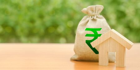 Wooden house figurine and a money bag with a Indian rupee symbol. Mortgage loan for the purchase of housing. Down payment first installment on the loan. Buying and selling, valuation of real estate.