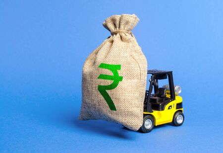 Forklift carries a huge money bag with the symbol of the Indian rupee. Budget and corruption, investment and economic growth. capital migration. Superprofits. Win a tender and get a contract