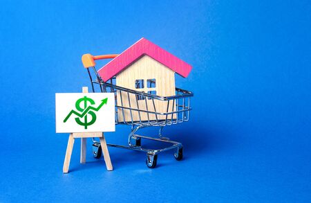A house in a shopping cart and an easel with a green up arrow chart. Market growth, attracting investment. Raising taxes and house maintenance. Real estate price increases. High demand and value Stockfoto