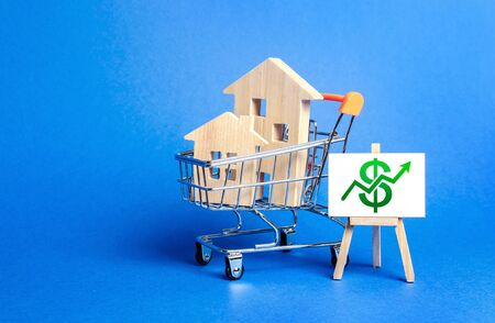 Houses in a shopping cart and an easel with a green up arrow chart. Market growth, attracting investment. Raising taxes and house maintenance. Real estate price increases. High demand and value Stockfoto
