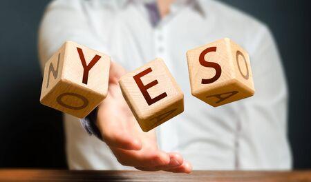 Ein Mann wirft Würfel mit Buchstaben und erfindet das Wort JA. Zustimmung und Annahme, beantworten Sie die Frage. Mut und Unwiderstehlichkeit, Eifer nach vorne, Zustimmung. Bestätigung und Annahme, Genehmigung Standard-Bild
