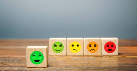 A series of blocks with faces from happy to angry. Happiness face selected. Concept of good rating, review and feedback. Satisfied customers and positive reviews, high popularity and attractiveness.
