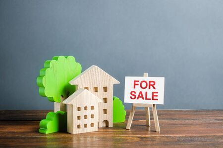 Figures of houses and an easel sign for sale. Buying and selling real estate, hot offers and property valuation. Smart investments and relocation. Good offer. Marketing advertising, attract customers.