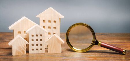 Magnifying glass and wooden houses. House searching concept. Home appraisal. Property valuation. Choice of location for the construction. Search for housing, apartments. Real estate