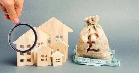 Bag with money and tape measure with a wooden houses. Property valuation. Limited real estate budget. Low subsidies. Lack of investment in construction. Market crisis. Reduced demand for home buying Stock Photo