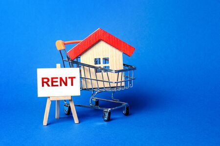 A house in a shopping cart and an easel with a word Rent. Rental housing and apartments, choice between buying and renting. Real estate prices and the desirability of buy a home or apartment.
