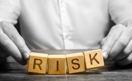 The man carelessly raises the word Risk. Caution and anticipation of possible problems and shocks. Planning and action strategy. Analytics. High risks in business, fragile balance and insecurity. Stock Photo