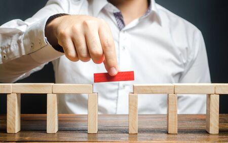 Un hombre está completando la construcción de un puente. Construye puentes, haz conexiones y contactos útiles. Mejorar y desarrollar un negocio. Nuevas soluciones innovadoras, crecimiento y prosperidad