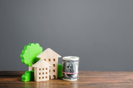 House figurines and a bundle roll dollars. Residential building maintaining cost, utility bills. Modernization housing, improving energy efficiency. Invest in real estate. Rental, apartment purchase. Stockfoto
